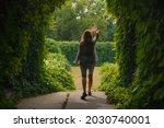 Young Woman Walking Into Green...