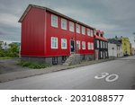 Typical house with red facade seen on most icelandic houses in reykjavik or other villages. View from  below with road and other houses..
