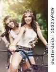 Two Boho Girls Riding A Bike