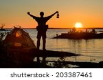 hiker in the sunrise with tent  | Shutterstock . vector #203387461