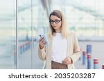 Small photo of portrait of a serious business woman with glasses blonde reads the news from a mobile phone uses the application to rewrite messages
