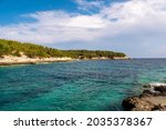 Srebrna Beach on the island of Vis in Croatia, seen from the other distant beach. Rocky shores of croatia, amazing blue sky and green pine trees.