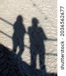 Small photo of Shadow on a well trodden beach of people leaning on railings