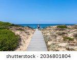 Woman Walks On Sand Dune In Sa...