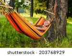 young woman lying in a hammock... | Shutterstock . vector #203768929