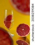 Small photo of A closeup shot of grapefruit slices and glasses of water on a specular surface against a yellow background