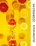 Small photo of A closeup shot of a glass of water on a specular surface and orange and grapefruit slices against a yellow background