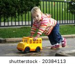 adorable baby girl pushing toy bus - stock photo