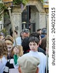 Small photo of Pontevedra, SPAIN - APRIL 17, 2014: A young acolyte with lanterns in hand, participating in an Easter procession through the city.