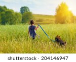 Stock photo little girl with dog walking on the field back to camera 204146947