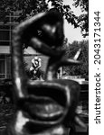 """Small photo of AMSTERDAM - AUGUST 25: view of famous statue of """"The Thinker"""" on August 25, 2021 in Amsterdam, The Netherlands.The Thinker is a world famous bronze sculpture made by Auguste Rodin (foreground blur)."""