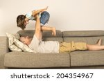 man lying on sofa and lifting... | Shutterstock . vector #204354967