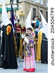 Small photo of Pontevedra, SPAIN - APRIL 17, 2014: A boy dressed acolyte wait between hooded, to march in the procession of Holy Week.