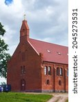 Small photo of KRASNOLESYE, RUSSIA - JUNE 12, 2016: Old red bricks church in Krasnolesye village (former Gross Rominten) of Kaliningrad Oblast. Now is the russian orthodox church of Holy Martyrs Adrian and Natalia.