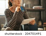 Small photo of Closeup on thoughtful young woman with credit card and tablet pc sitting on divan