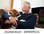 Stock photo senior man relaxing at home with pet dog 204839221