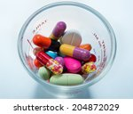 many colorful pills in a cup of ... | Shutterstock . vector #204872029