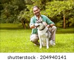 Stock photo man and husky dog walk in the park 204940141