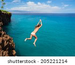 Woman Jumping Off Cliff Into...