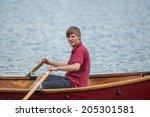 Teenage Boy Rowing A Boat On A...