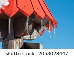 Shiny Icicles On A Red Wooden...