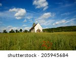 11th Century Church. Distant view looking across a wild flower meadow. Red poppies contrasting with a blue sky. Saint Hubert