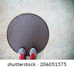 A Pair Of Feet On A Manhole...