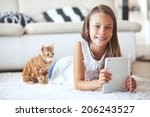 Stock photo pre teen girl playing on tablet pc laying down on a white carpet at home 206243527