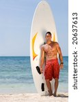 male at the beach standing next to his surfboard - stock photo