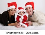 Young couple with baby dressed in Santa hats - stock photo