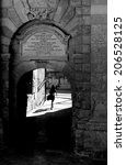 Small photo of Single woman going in arch in a shadow in Birgu, Malta, Europe, loneliness, woman going, black and white contrast photo, solitude mood, solitude, street in Malta