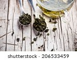 Stock photo cup of green tea and spoons on rustic wooden table 206533459