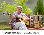 Old man playing acoustic guitar with closed eyes in his garden