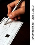 A macro shot of a person writing a check. - stock photo
