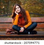 Happy Girl On Bench In Autumn...
