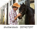 young horse breeder comforting a horse in stable - stock photo