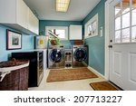 Stock photo light blue laundry room with modern steel appliances and white cabinets 207713227