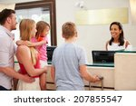 Stock photo family checking in at hotel reception 207855547