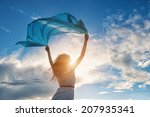 Stock photo beautiful young woman on sunset background with blue tissue 207935341