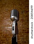 A vintage microphone in front of a brick wall - stock photo