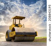 Small photo of Road roller at road construction site with cloudy blue sky during sunset