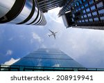 LONDON, UK - JULY 20, 2014: Aircraft over the London's skyscrapers going to land in the City airport - stock photo