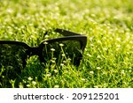 black pair of sunglasses laying ... | Shutterstock . vector #209125201