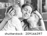 two daughters kissing their... | Shutterstock . vector #209166397