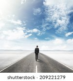 Businessman Walking On Road In...