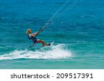 a young woman kite surfer rides ... | Shutterstock . vector #209517391