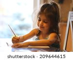 cute girl painting a picture  | Shutterstock . vector #209644615