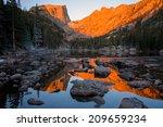The sun rises over a mirror-like Dream Lake, bathing Hallett Peak in a dramatic red/orange sunrise light.