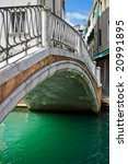 Nice stone bridge over green water of a venetian canal, Italy - stock photo