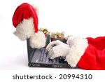 Santa Claus typing using laptop with santa claus hat being put on laptop lcd corner and presents in the background - isolated on white - stock photo